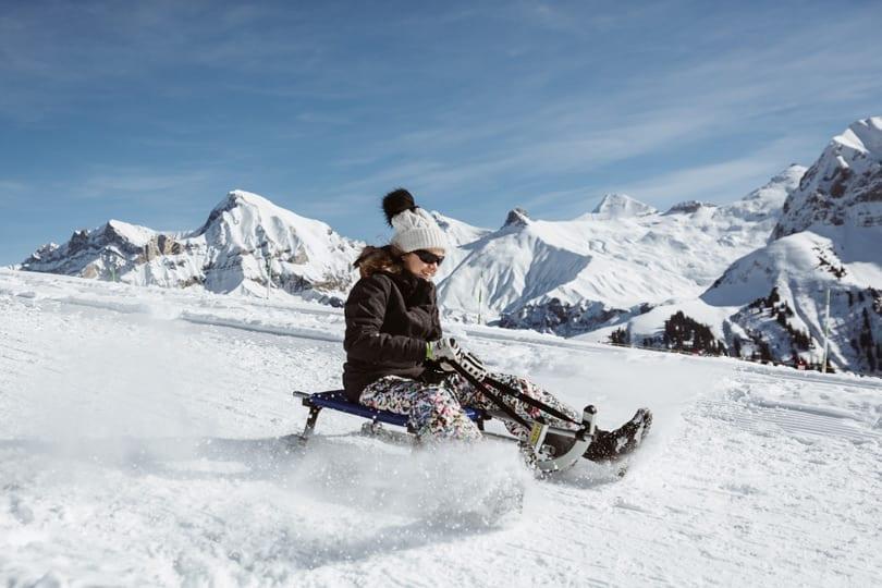 Mädchen am Schlitteln vor herrlichem Bergpanorama am VogellisiBerg