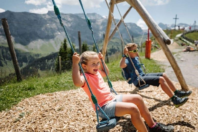 Kinder schaukeln auf dem Spielplatz auf Sillerenbühl in Adelboden