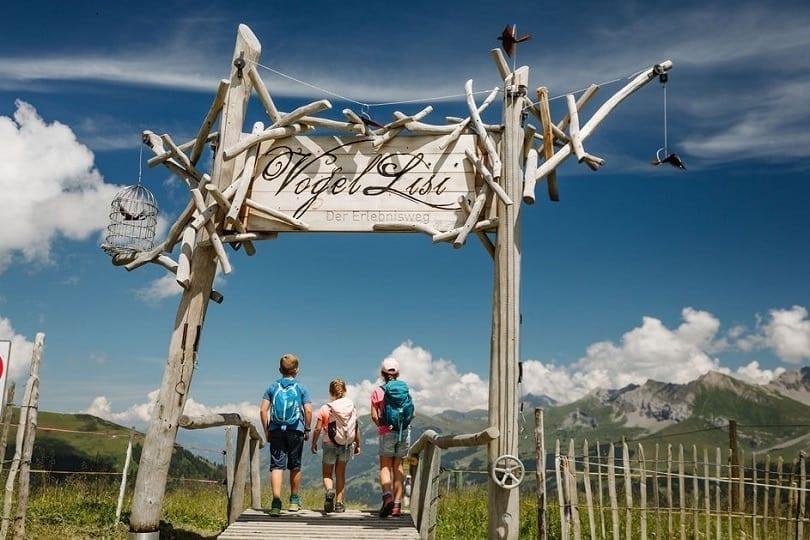 Drei Kinder gehen durch das Eingangstor des Vogellisi Erlebnisweg