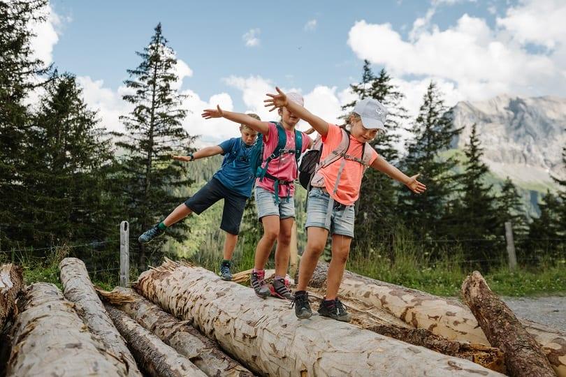 Kinder balancieren auf gefälltem Holz